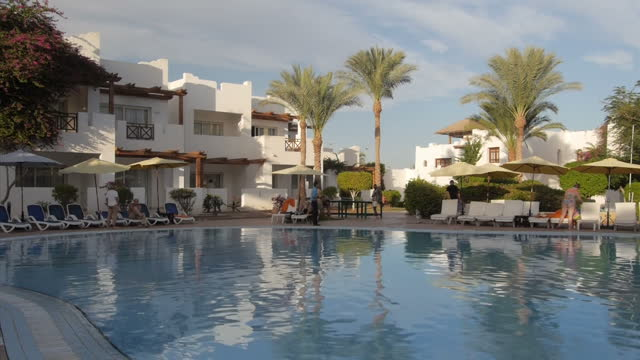vidéos et rushes de exterior shots of tourists relaxing around a swimming pool at a resort hotel and hotel workers carrying out cleaning tasks on november 08, 2014 in... - station de vacances