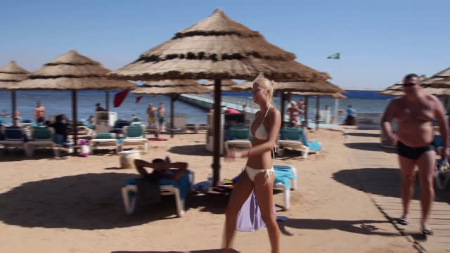 exterior shots of tourists sunbathing on a beach in sharm el sheikh and a plane passing overhead on november 05 2015 in sharm ash shaykh egypt - land stock videos & royalty-free footage