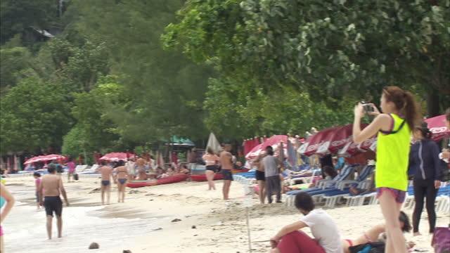 exterior shots of tourists sunbathing on the beach, sitting ion beach cafes and people enjoying water sports on august 27, 2014 in koh phi phi don,... - provinsen krabi bildbanksvideor och videomaterial från bakom kulisserna