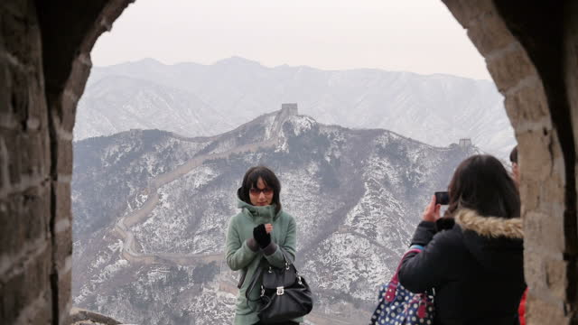 exterior shots of tourists walking along the badaling section of the great wall of china and taking photographs with the wall and snowcovered... - badaling stock videos and b-roll footage