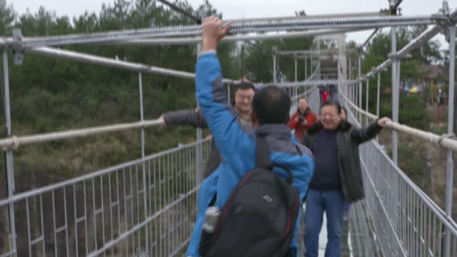 exterior shots of tourists walking along the haohan qiao glassbottomed suspension bridge in shiniuzhai national geological park including one man... - 自重トレーニング点の映像素材/bロール