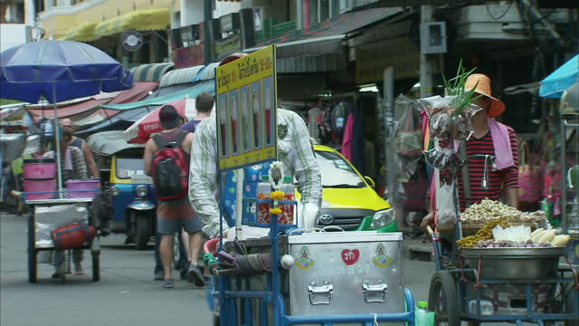 stockvideo's en b-roll-footage met exterior shots of tourists walking through backpacking district past various tourist businesses street food vendors etc along khao san road on may 23... - staatsgreep