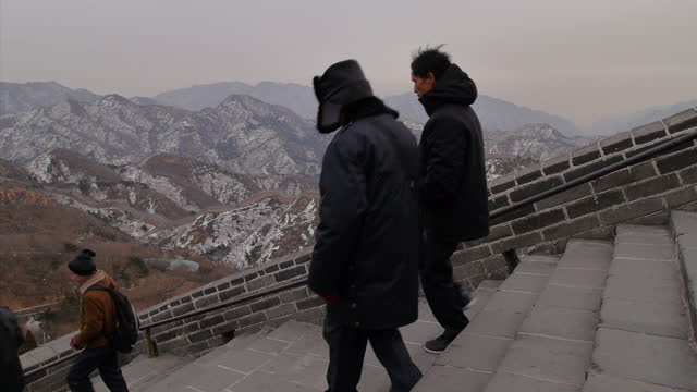 exterior shots of tourists walking up and down the badaling section of the great wall of china with views of the snowcovered surrounding landscape... - badaling great wall stock videos & royalty-free footage