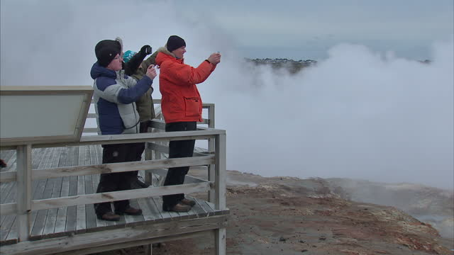 Exterior shots of tourists watching geysers or geothermal steam vents from a viewing platform taking pictures and looking at social media on their...