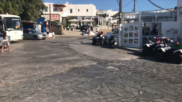 exterior shots of traditional white painted buildings and tourists walking and cars and taxis driving through square on 22 august 2020 in mykonos... - mykonos stock videos & royalty-free footage