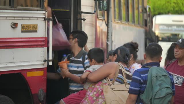 exterior shots of traffic and pedestrians during rush hour with people scrambling on board buses on april 04 2018 in san salvador el salvador - scrambling bildbanksvideor och videomaterial från bakom kulisserna