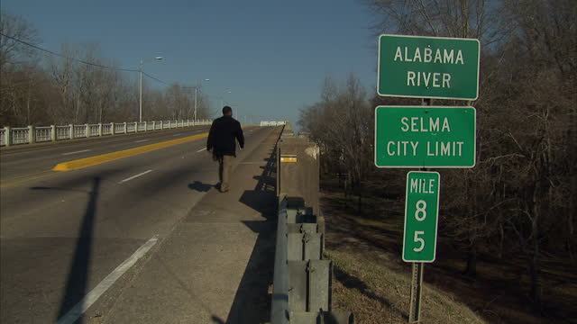 Exterior shots of traffic crossing the Edmund Pettus Bridge including shots of signs for the Alabama River and Selma City Limit and a pedestrian...