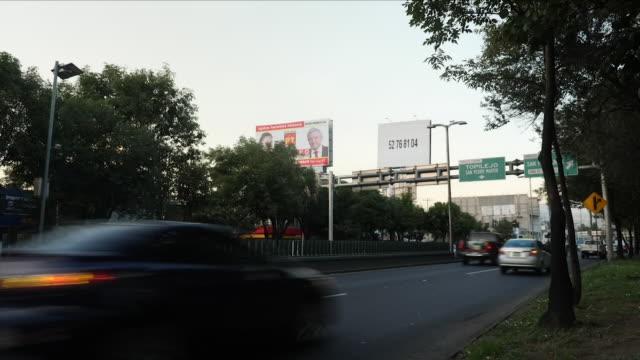 vídeos de stock, filmes e b-roll de exterior shots of traffic in mexico city passing a large election poster for andrés manuel lópez obrador on 2 july 2018 in mexico city mexico - eleição
