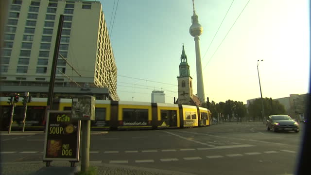vídeos de stock, filmes e b-roll de exterior shots of traffic passing along spandauer strasse in berlin with st marienkirche and the berliner fernsehturm in the background - torre de televisão berlim