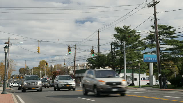 exterior shots of traffic passing an intersection on green and roadside businesses on 12 december 2017 in brentwood, new york, united states - long island video stock e b–roll
