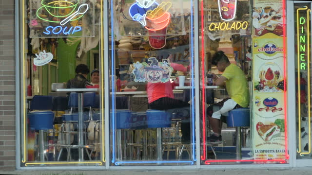 exterior shots of traffic through brentwood and a bakery with people visible through windows 'la espiguita bakery' on 12 december 2017 in brentwood... - porta della cella video stock e b–roll