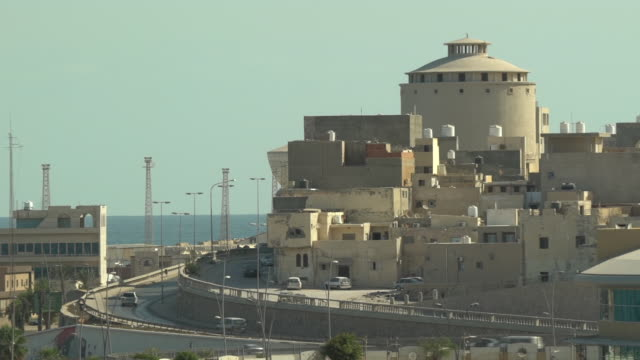 exterior shots of tripoli port, cars driving along roads by the sea, large crane and passing traffic, small boats out at sea on 21st september in... - old town stock videos & royalty-free footage