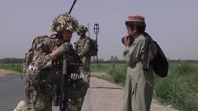 exterior shots of troops from the welsh guards regiment meeting afghan national police guards patrolling in helmand sky news afghanistan general... - regiment stock videos & royalty-free footage