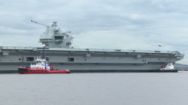 vidéos et rushes de exterior shots of tugboats towing the hms queen elizabeth aircraft carrier away from dock and towards the firth of forth including shots of the... - remorqueur