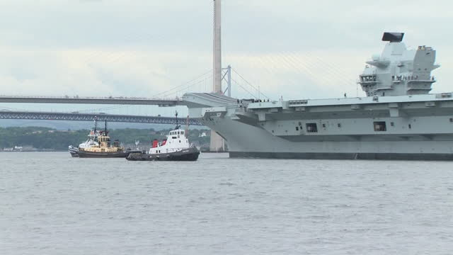 exterior shots of tugboats towing the hms queen elizabeth aircraft carrier away from dock and towards the firth of forth including shots of the forth... - firth of forth bildbanksvideor och videomaterial från bakom kulisserna