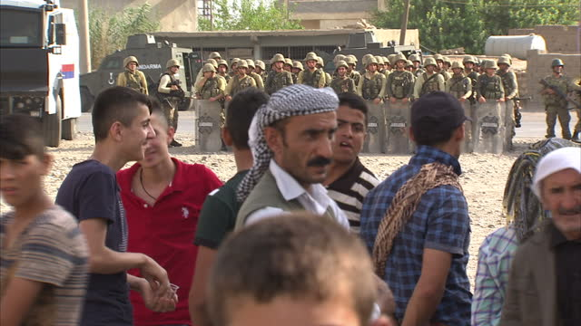 exterior shots of turkish soldiers in the town of silopi with riot shields stood in a line opposite a group of kurdish people after clashes between... - silopi stock videos and b-roll footage