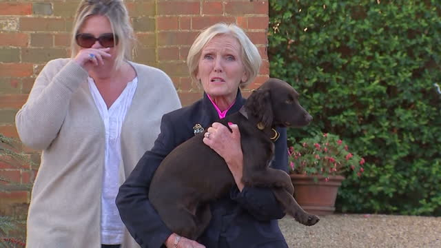 Exterior shots of TV celebrity chef Mary Berry walking from her house and posing for photos holding a dog before walking back in through gates on...