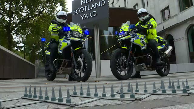 Exterior shots of two Metropolitan Police officers posing on new motorcycles outside new Scotland Yard including shots with an example of a remote...