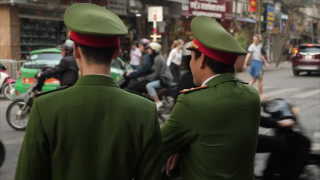 exterior shots of two policemen watching tuk tuk's scooters cars and pedestrians pass through a busy hanoi city centre junction during a summit... - 首脳会議点の映像素材/bロール