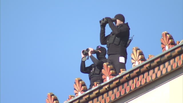 exterior shots of two secret service men on rooftop watching a protest by anti nsa campaigners in the streets below with binoculars on january 17... - 礼拝点の映像素材/bロール