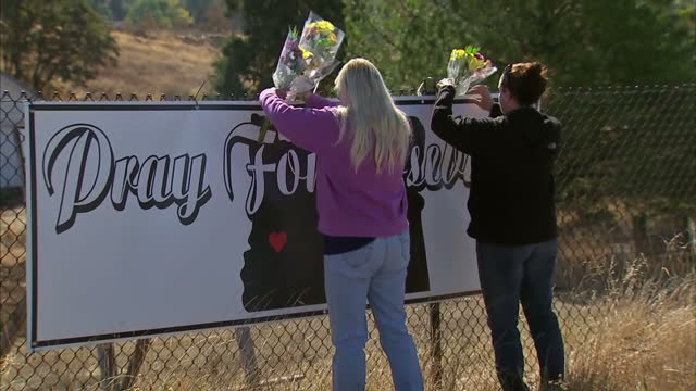 exterior shots of two women leaving floral tributes at a sign with the slogan pray for roseburg near umpqua community college where nine people were... - community college stock videos & royalty-free footage