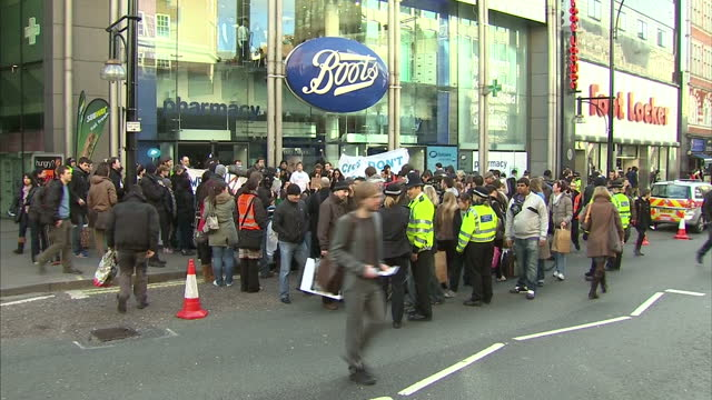 vidéos et rushes de exterior shots of uk uncut protesters demonstrating outside a boots store on oxford street exterior shots of protesters with banners and loudhailers... - récession