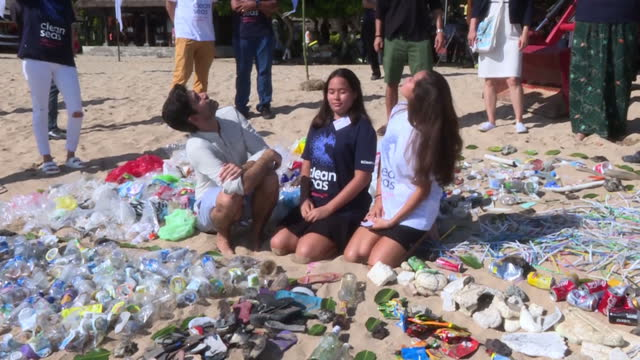 Exterior shots of UN Clean Seas campaigners and other officials taking part in a beach cleanup during the World Ocean Summit in Bali and posing for...