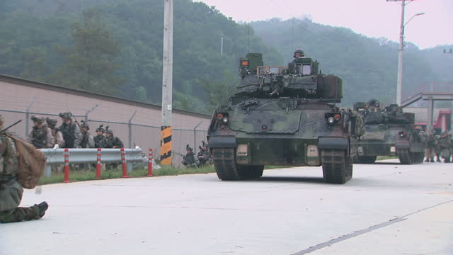 exterior shots of us and south korean soldiers taking part in a joint training exercise running alongside a tank in gas masks on 20 september 2017 in... - 韓国点の映像素材/bロール