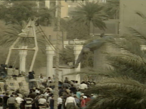 vídeos de stock e filmes b-roll de exterior shots of us army and iraqi locals pulling down statue of saddam hussein with rope around neck and then jump on statue celebrating the fall... - estátua
