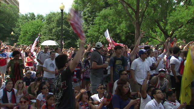 exterior shots of us football fans in a washington dc park in the buildup to the usa v germany world cup clash cheering waving stars and stripes... - internationaler fußball stock-videos und b-roll-filmmaterial