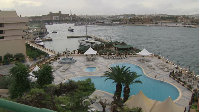 stockvideo's en b-roll-footage met exterior shots of valetta including flags flying a hotel swimming pool and views over the harbour on 4 october 2017 in valetta malta - valletta