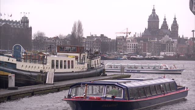 Exterior shots of various boats barges etc moored and sailing along canal by the National Maritime museum on March 16 2010 in Amsterdam Netherlands