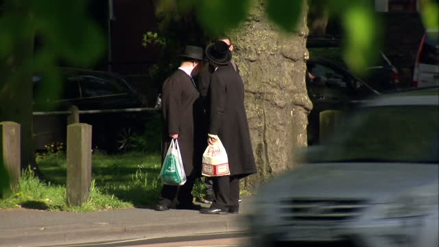 stockvideo's en b-roll-footage met exterior shots of various hasidic jewish people walking along the streets of stamford hill on may 16 2016 in london england - orthodox jodendom
