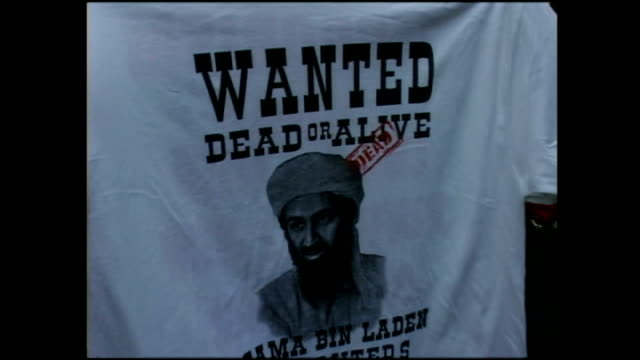 vidéos et rushes de exterior shots of various sidewalk vendors selling 9/11 themed tshirts stars and stripes flags and 'wanted' tshirts featuring osama bin laden on... - vendeur ambulant