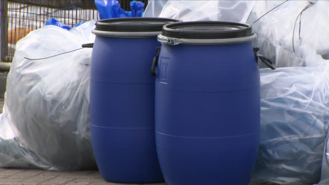 exterior shots of various waste rubbish and blue barrel waste containers outside the forensics search tent at the ashley wood recovery garage on the... - festzelt stock-videos und b-roll-filmmaterial