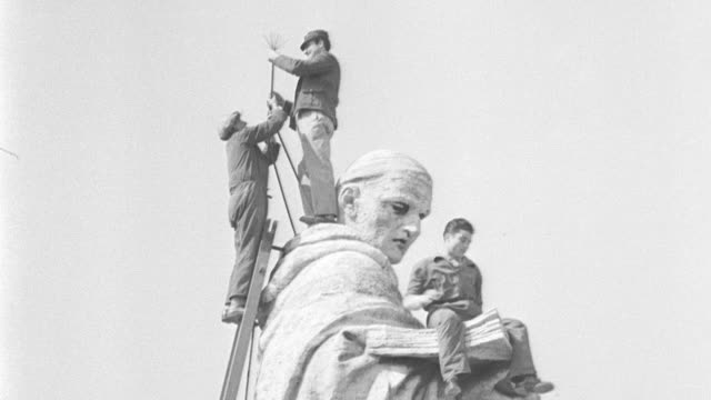 vídeos de stock, filmes e b-roll de exterior shots of vatican and basilica / men on roof cleaning and repairing statues of saints. vatican cleans church in preparation for holy year... - 1933