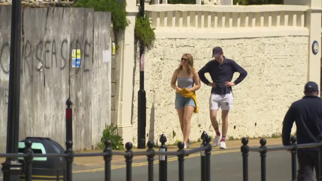exterior shots of ventnor seafront on the isle of wight with a few people walking on the promenade waves rolling in to the beach and woman sat on the... - isle of wight stock videos & royalty-free footage