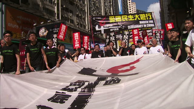 exterior shots of very large crowds of prodemocracy protesters marching in protest through the streets of hong kong with banners reading 'march for... - 2014 stock videos and b-roll footage