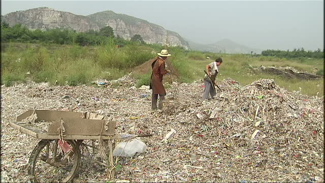 exterior shots of villagers using a rake to sift through plastic and other waste material in a landfill on august 23 2008 in dongzhuang village china - 河南省点の映像素材/bロール