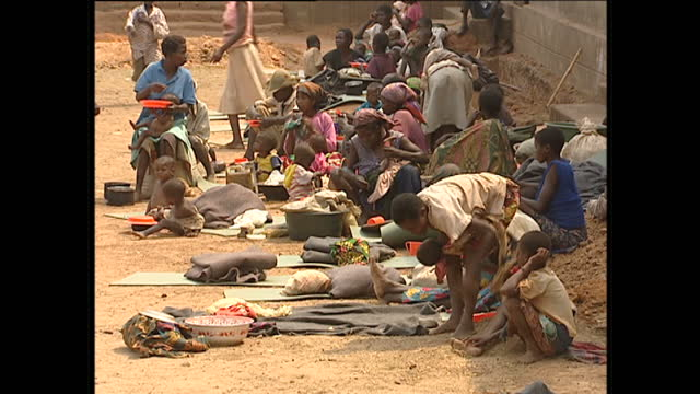 exterior shots of villagers waiting in line with plates for a food handout and women with children eating on August 21 2001 in Angola