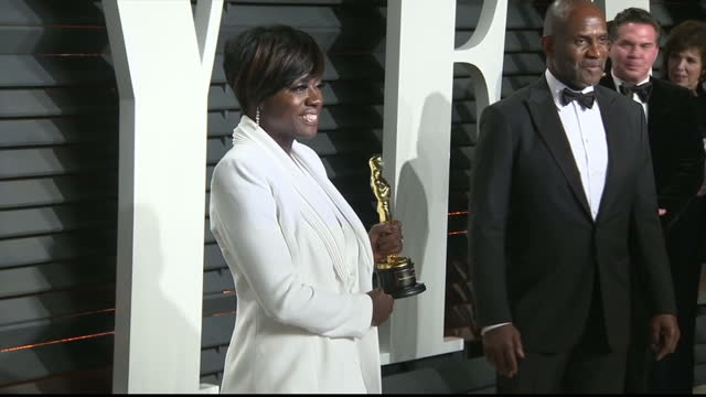 vídeos de stock e filmes b-roll de exterior shots of viola davis arriving at the vanity fair oscar party and posing with her oscar award for best actress in a supporting role - festa do óscar