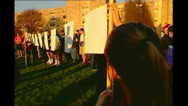 exterior shots of virginia tech students hanging up white bunting in a vigil to the victims of a massacre by seung-hui cho on april 24, 2007 in... - 追悼行事点の映像素材/bロール