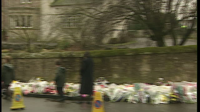 exterior shots of visitors looking at floral tributes left outside dunblane primary school for the victims of the shootings and sikh men saying a... - ダンブレーン点の映像素材/bロール