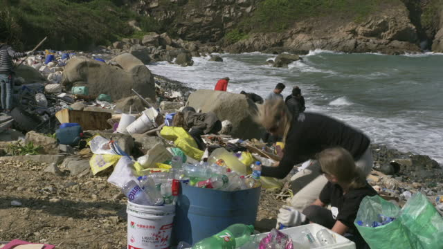Exterior shots of volunteers on a rocky beach in Hong Kong cleaning up plastic debris on January 24 2017 in Hong Kong China