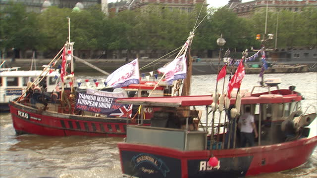 exterior shots of vote leave and vote remain campaign boats in the river thames outside of houses of parliament zoom in to people observing from... - 2016 european union referendum stock videos and b-roll footage