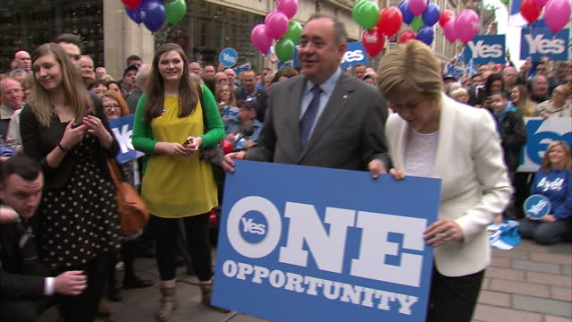 "exterior shots of vote yes campaigners holding ""yes"" posters & flags at a campaigning event & alex salmond & nicola sturgeon posing for... - 2014 stock-videos und b-roll-filmmaterial"