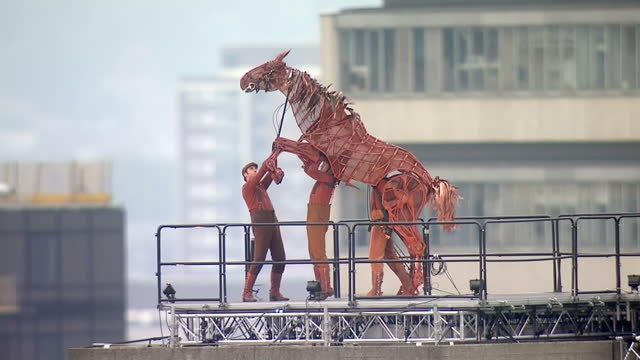 Exterior shots of War Horse puppet galloping out on platform outside National Theatre with hots of Quenn Elizabeth and other Royal Family members...