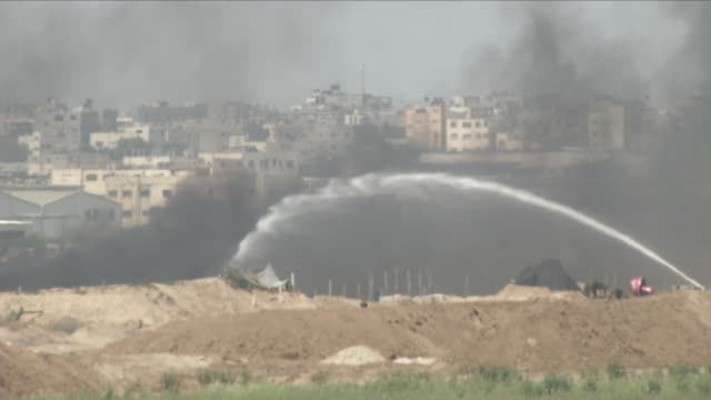 exterior shots of water being sprayed on rising thick black smoke with a large crowd of protesters gathered at the israeli / gaza border on 6th april... - 2018 gaza border protests stock videos & royalty-free footage