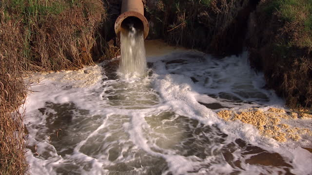 exterior shots of water rushing out of pipe from gold mine into pool gold mining causing acid pollution to water on september 23, 2010 in... - 酸点の映像素材/bロール