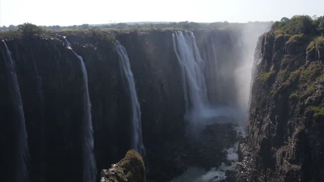 exterior shots of water tumbling over victoria falls on the zambezi river with clouds of spume or spray in the air on august 07 2015 in hwange... - victoria falls stock videos and b-roll footage